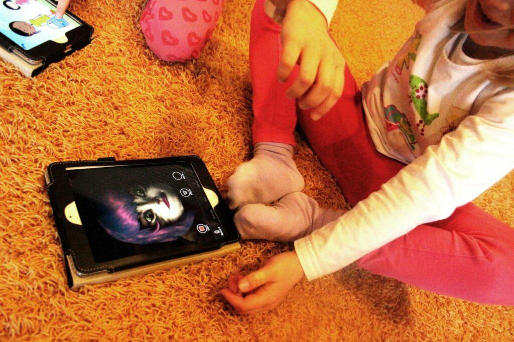 Kuva 1. Esikoululainen pelaa päiväkodin iPadilla peliä, jossa meikataan kissa